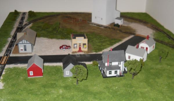 Here you can see a few of the details I've added.  There are now trees behind some of the houses; there's a car and a man by the store; and a truck an